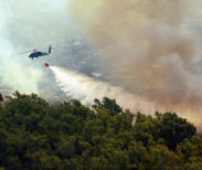 An MH-60S Seahawk helicopter assigned to Helicopter Sea Combat Squadron (HSC) Eight Five dumps water from a 420-gallon extinguishing trough October 23, 2007, onto of one of the many areas in San Diego County, California, suffering from an ongoing wildfire. The trough is used to dump water to help fend off the fires that have already forced more than 250,000 people from their homes.