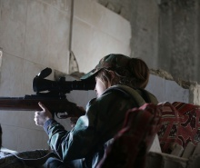 A female Syrian sniper from the Republican Guard commando battalion aims fire during clashes with rebels in the restive Jobar area, in eastern Damascus, on March 25, 2015. (Joseph Eid/AFP Photo)