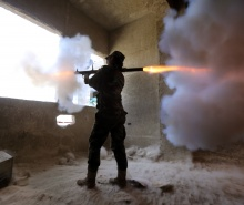 A female Syrian soldier from the Republican Guard commando battalion fires a rocket-propelled grenade (RPG) during clashes with rebels in the restive Jobar area, in eastern Damascus, on March 25, 2015. (Joseph Eid/AFP Photo)